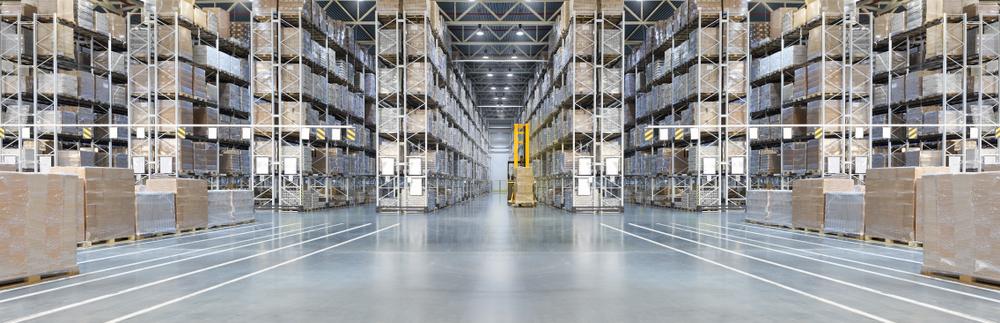 Stort distributionslager med höga hyllor och lastare