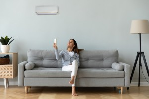 Smiling,Woman,Using,Air,Conditioner,Remote,Controller,,Sitting,On,Cozy